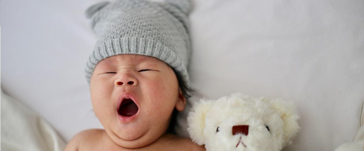 Bébé avec son bonnet naissance et son doudou